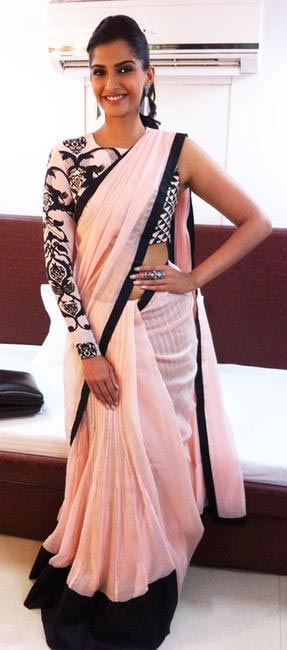 A baby pink and black net saree by Payal Singhal with full sleeve one shoulder printed blouse. She accessorizes with a metal long ring and a pair of...