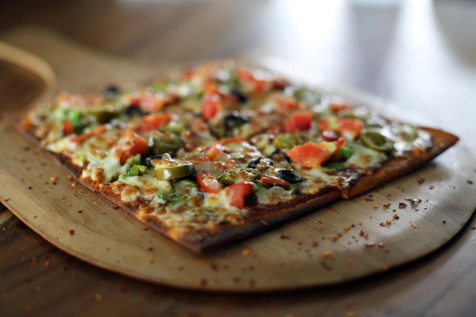 Black olive & jalapeno pizza on parmesan flatbread